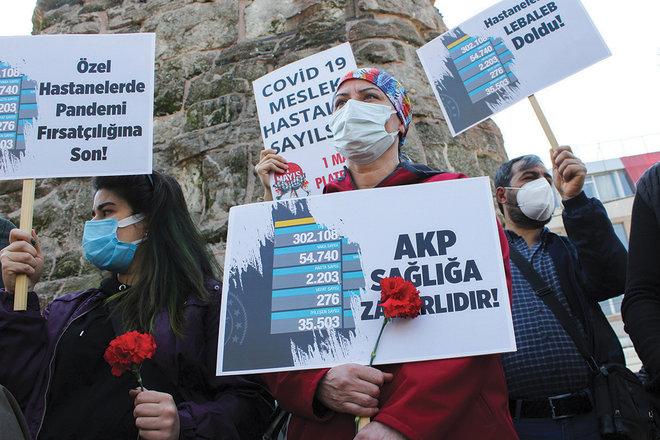 عامل يحمل لافتة كتب عليها «حزب العدالة والتنمية ضار بالصحة» خلال مظاهرة لتحسين ظروف العمل في تركيا