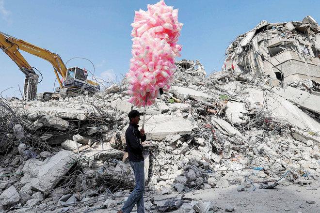 فلسطيني يسير بأكياس حلوى أمام أنقاض مبنى دمرته الغارات الإسرائيلية
