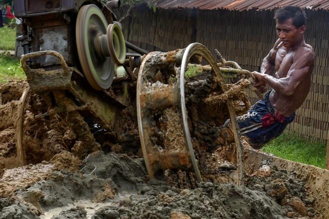 عامل يخلط مواد لصنع الطوب في أحد المصانع في ضواحي مدينة كاجو الإندونيسية