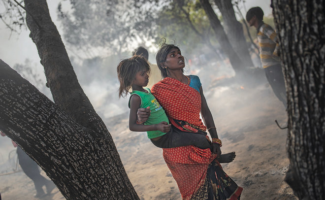 امرأة تحمل ابنتها بعيدا عن آثار حريق اندلع في إحدى ضواحي الهند الفقيرة