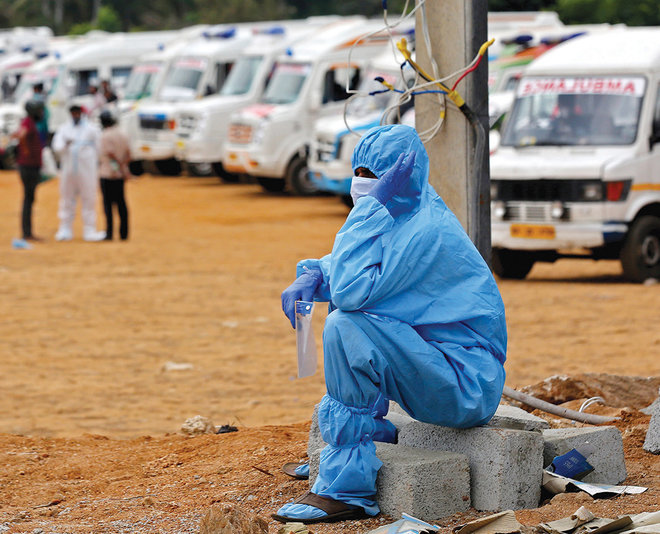 رجل يرتدي لباس الحماية الشخصية أثناء انتظاره لإحراق جثث أقاربه في موقع حرق جثث جماعية في مدينة بنجالور الهندية