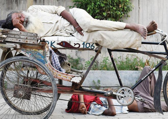 رجل ينام على دراجته وآخر على الأرض في طريق عام في مدينة أمريتسار الهندية