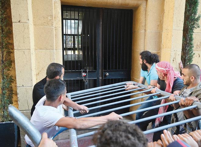 متظاهرون يحاولون اقتحام بوابة وزارة الاقتصاد اللبنانية خلال احتجاج على انقطاع التيار الكهربائي