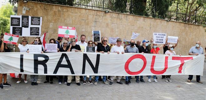متظاهرون لبنانيون يحملون لافتات ضد تدخلات إيران أمام السفارة الفرنسية في بيروت