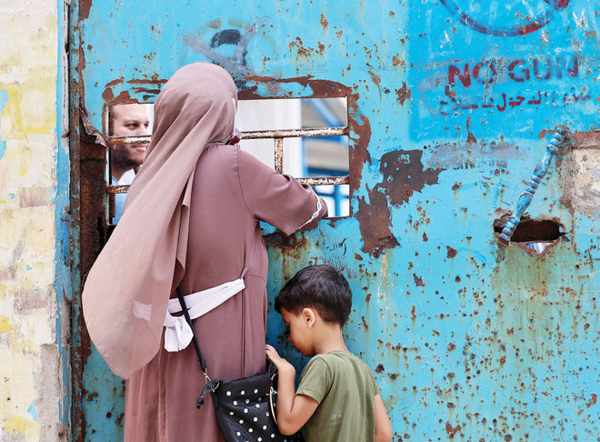 فلسطينية وطفلها يقفان أمام نافذة مركز توزيع مساعدات