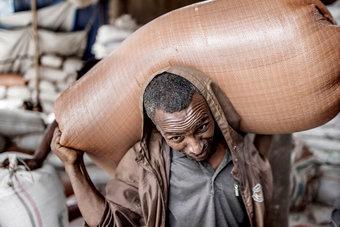 عامل يحمل كيسا من التيف الأحمر «أحد أنواع الشاي » في مستودع في العاصمة الإثيوبية